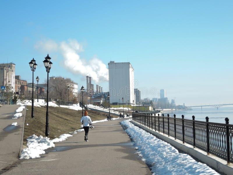 De meisjeslooppas langs de de lentedijk op een de lentedag royalty-vrije stock foto's