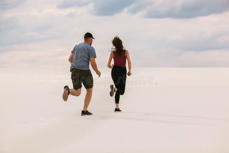 De meisjeslooppas vanaf de kerel in de woestijn, de man wil haar inhalen, is het meisje bang en loopt vanaf hem royalty-vrije stock foto