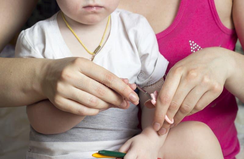 De meisjesmoeder snijdt haar spijkers in de Kaukasische handen van een klein meisje, stock fotografie