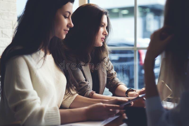 De meisjesontwerpers kleedt het werken samen met multimedia en tekstinhoud gebruikend technologie en wifi stock fotografie