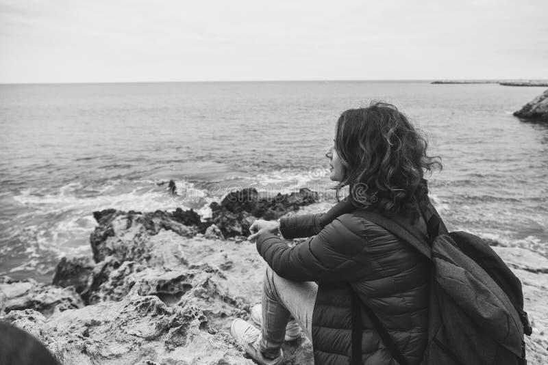 De meisjesreiziger zit op de rotsen op de oceaan en let op lan royalty-vrije stock foto's