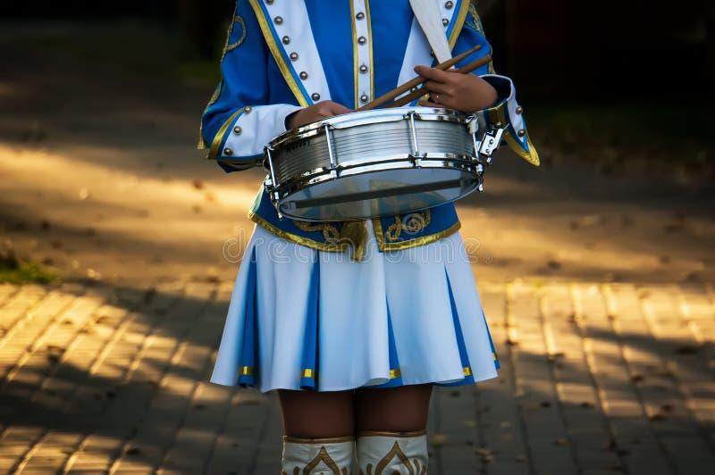 De meisjesslagwerker houdt een trommel en trommelstokken ter beschikking bij de parade op de straat stock foto's