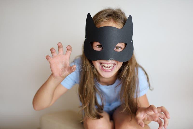 De meisjesspelen in een zelf-gemaakt masker van zwarte kat royalty-vrije stock fotografie