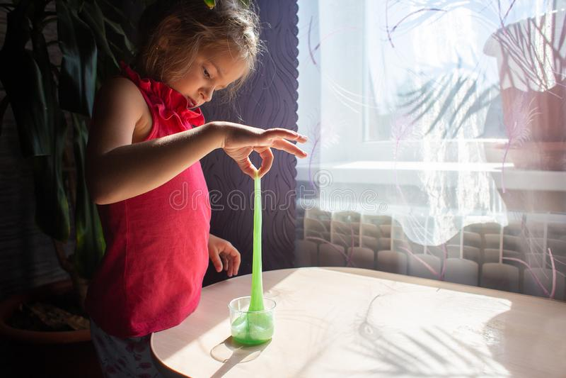 De meisjesspelen met een tegenovergesteld stuk speelgoed - een groen slijm Het uitgerekte slijm royalty-vrije stock foto's