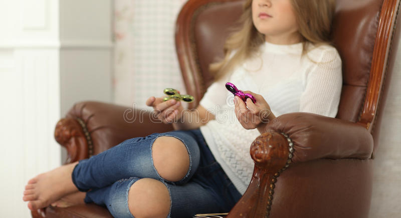 De meisjesspelen met Fidget Spinners in handen, het concept het verlichten van spanning, ontwikkelen een kleine handwiskunde stock foto