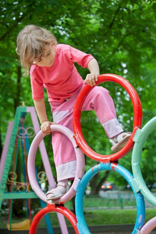 De meisjesspelen op de speelplaats van kinderen stock fotografie