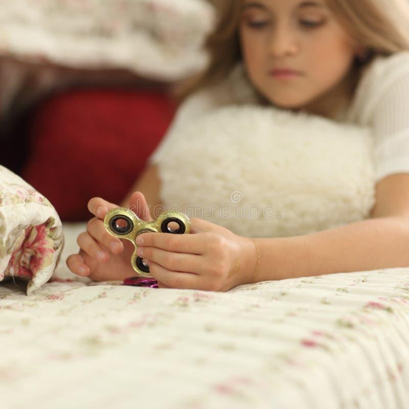 De meisjesspelen thuis met Fidget Spinners in handen, het concept het verlichten van spanning, ontwikkelen een kleine handwiskund royalty-vrije stock afbeeldingen