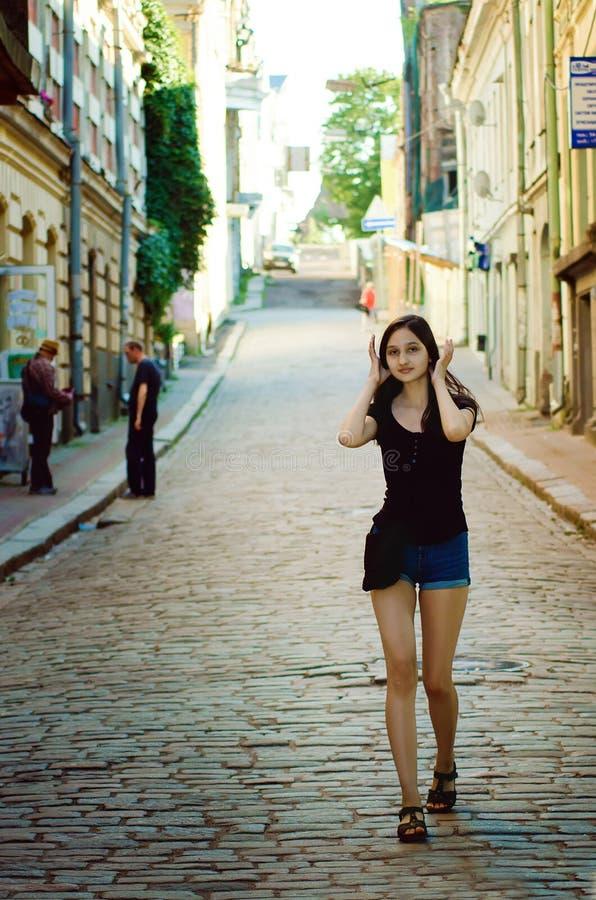 De meisjestiener in een T-shirt en borrels loopt onderaan de straat stock afbeelding