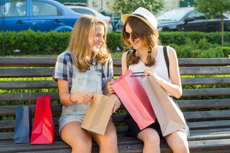 De meisjestieners zitten op een bank in de stad en bekijken aankopen in het winkelen zakken royalty-vrije stock foto
