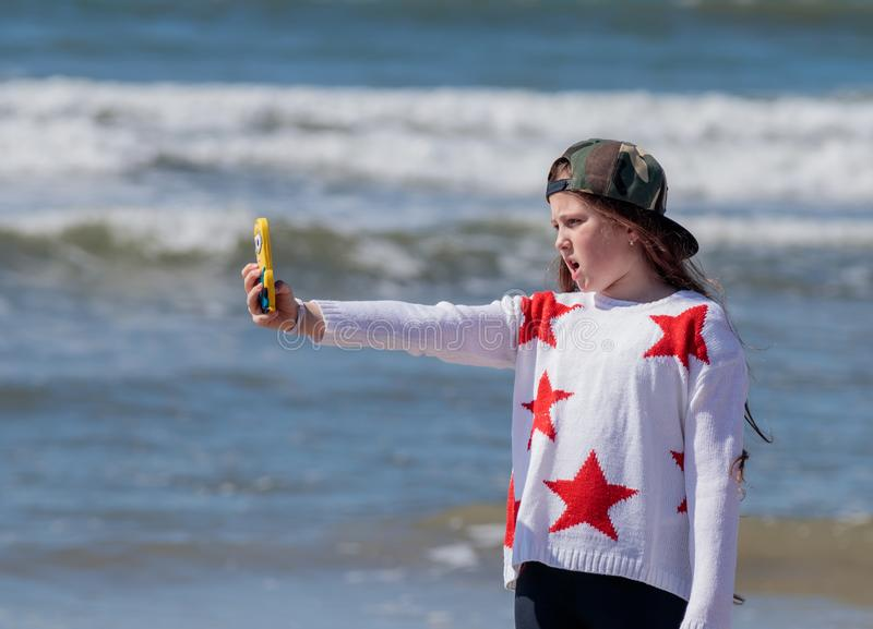 De meisjestribunes op het strand en maakt selfie gebruikend uw mobiele telefoon royalty-vrije stock afbeelding