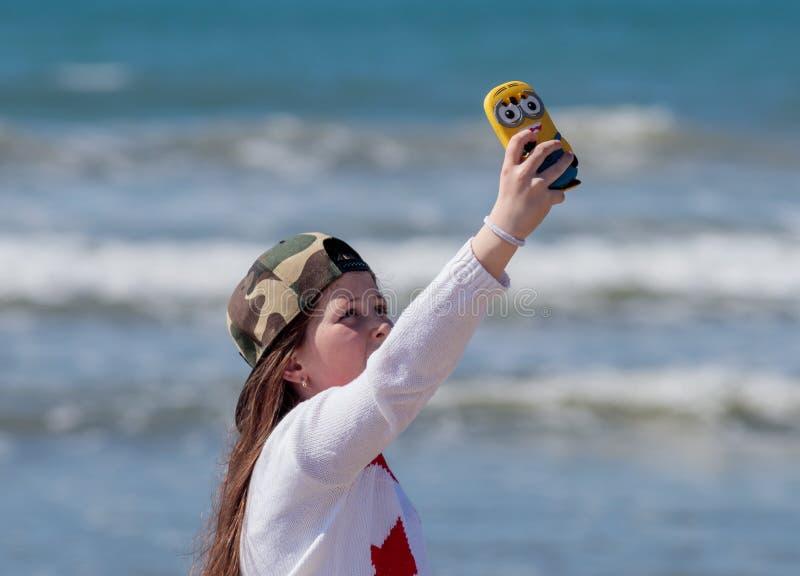 De meisjestribunes op het strand en maakt selfie gebruikend uw mobiele telefoon royalty-vrije stock afbeeldingen