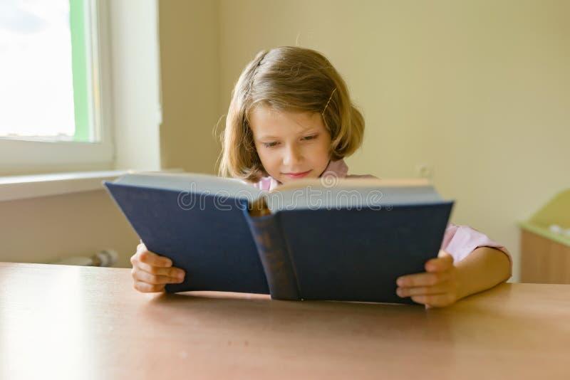 De meisjestudent zit bij een bureau met boek School, onderwijs, kennis en kinderen royalty-vrije stock foto