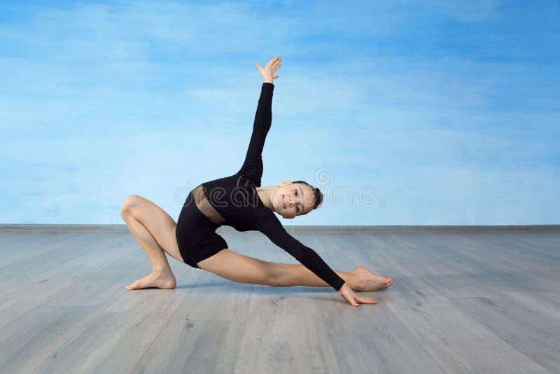 De meisjesturner in een zwart gymnastiek- badpak glimlacht en toont een gymnastiek- oefening op de vloer stock afbeeldingen