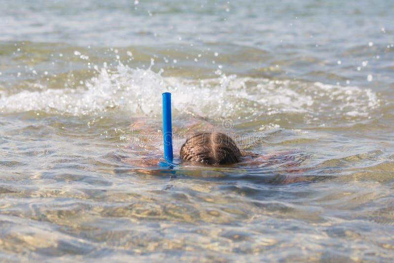 De meisjesvlotters op het water met masker en snorkelen stock foto's