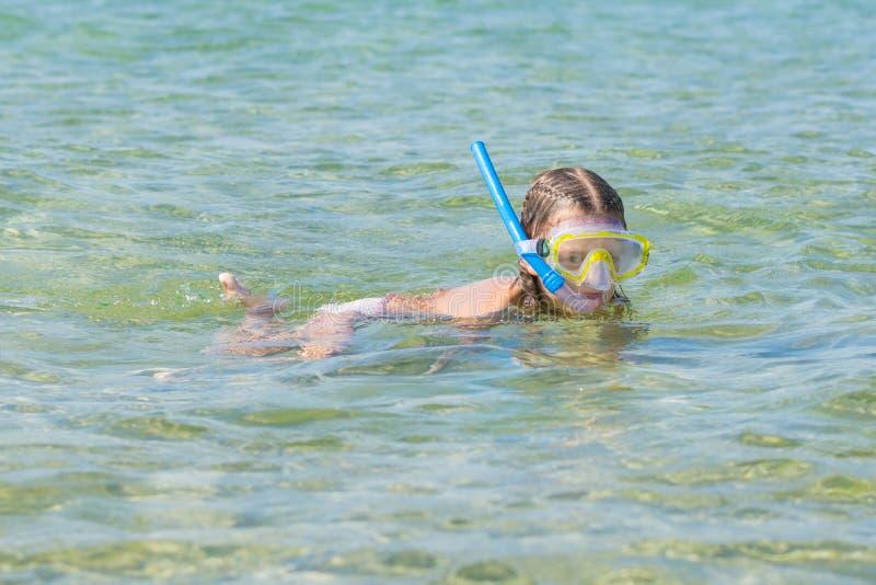 De meisjesvlotters over het water met masker en snorkelen royalty-vrije stock afbeeldingen