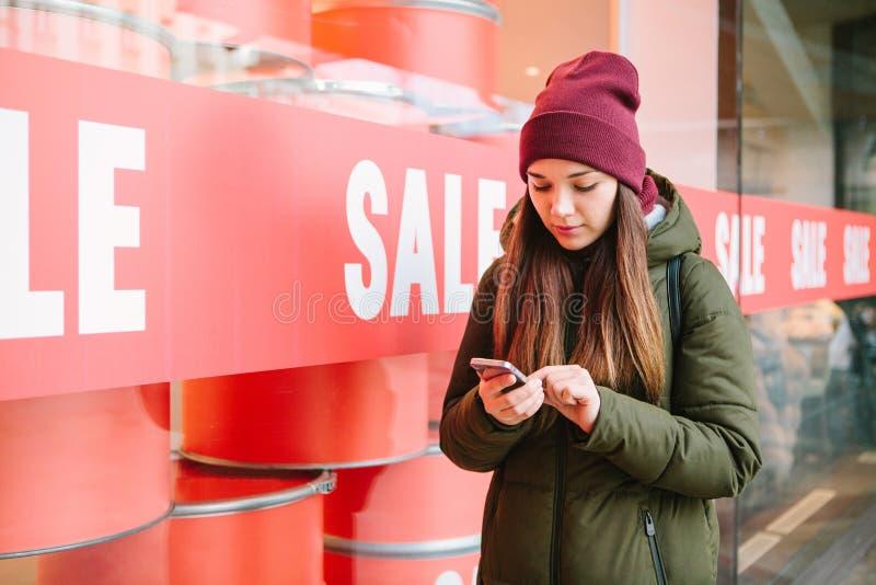 De meisjesvraag telefonisch om online goederen te raadplegen of te selecteren op verkoop royalty-vrije stock afbeelding