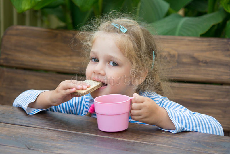 De meisjeswafel van vier jaar bijt en drinkt thee royalty-vrije stock foto