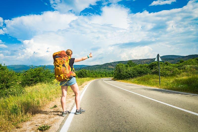 De meisjeswandelaar houdt de auto op de weg tegen stock afbeeldingen