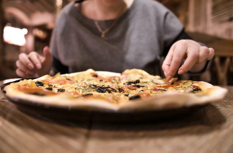 De meisjeszitting in een koffie neemt een plak van pizza, close-up stock afbeeldingen