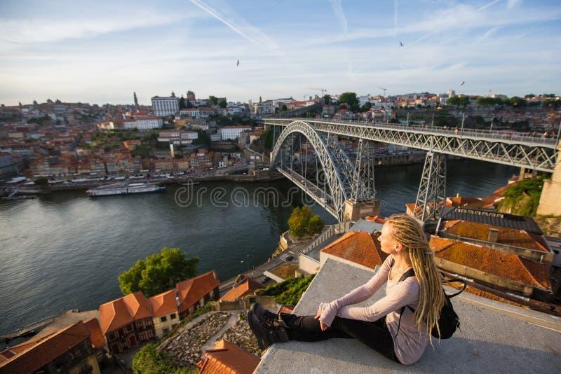 De meisjeszitting op het hoogste observatiedek op Douro-rivier en Dom Luis I overbruggen, Porto stock afbeelding