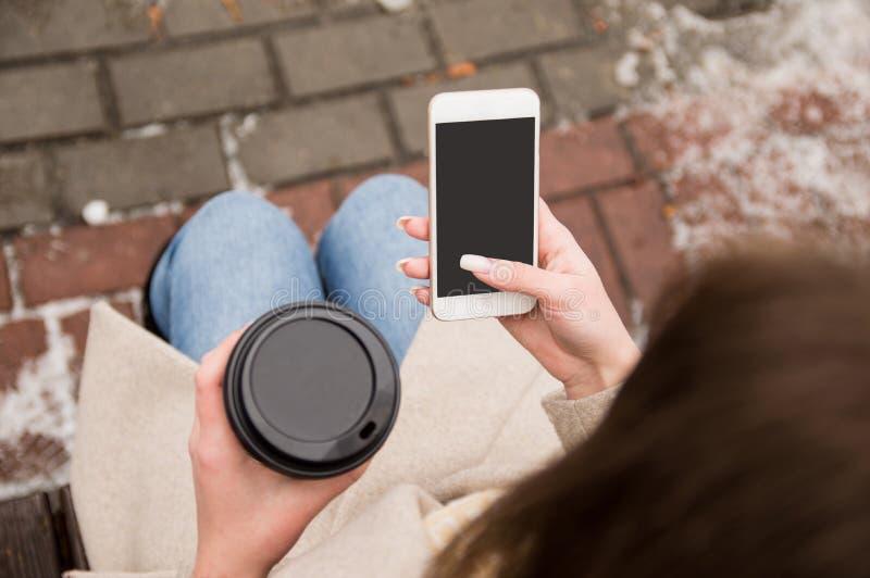 De meisjeszitting op de straat met een telefoon en koffie in haar handen, onderzoekend de telefoon, die op een vraag wachten, het stock foto