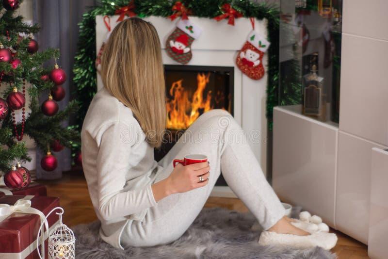 De meisjeszitting verfraaide dichtbij open haard en Kerstboom stock foto's
