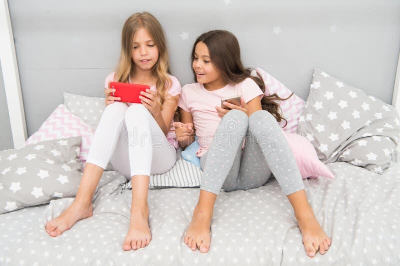 De meisjeszusters dragen pyjama bezig met smartphones De kinderen in pyjama gaan met smartphones interactie aan Toepassing voor j royalty-vrije stock fotografie