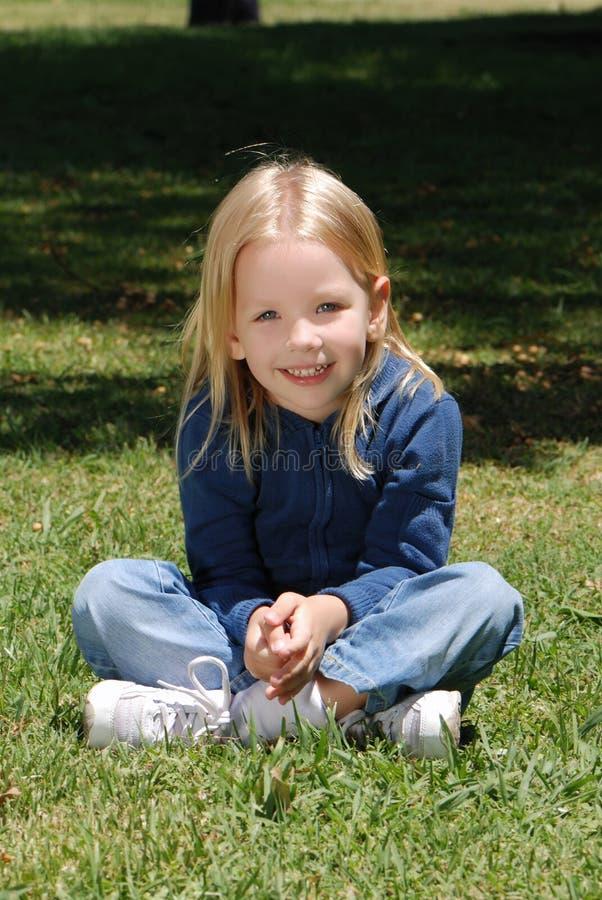 De meisjezitting op een gras royalty-vrije stock foto