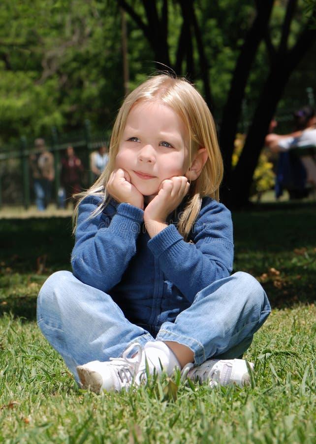 De meisjezitting op een gras royalty-vrije stock foto's