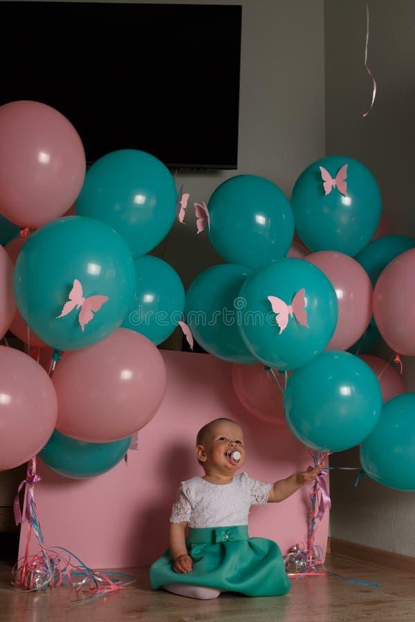 De meisjezitting op de vloer in de ruimte naast de ballons, eerste verjaardag, viert één van het blauwe en roze ballenéénjarige v stock foto