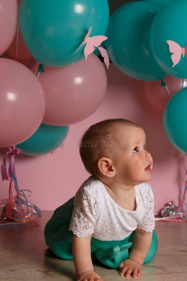De meisjezitting op de vloer in de ruimte naast de ballons, eerste verjaardag, viert één van het blauwe en roze ballenéénjarige v stock fotografie
