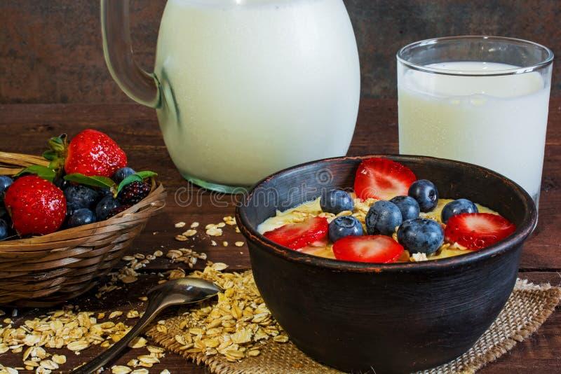 De melk in een kruik en havermeelhavermoutpap met glas melk in een aardewerk werpt met verse rijpe berrie royalty-vrije stock foto's