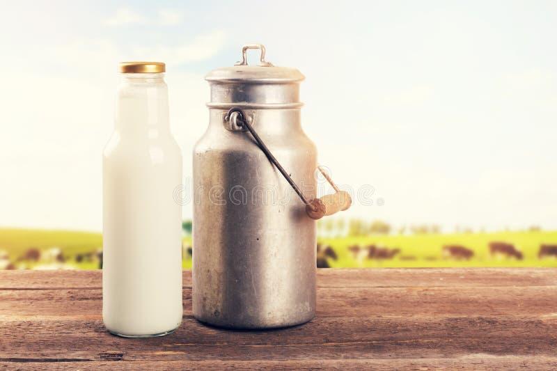 De melk kan en op lijst dichtbij de weide van het koeweiland bottelen stock fotografie