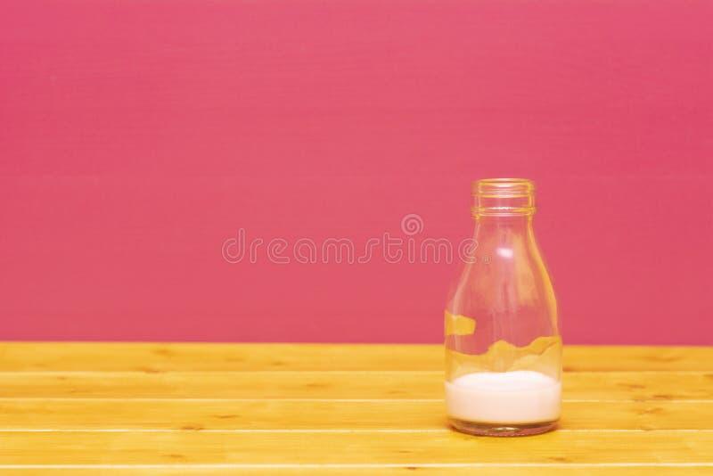 De melkfles van de één derdepint met residu's van aardbeimilkshake stock foto's