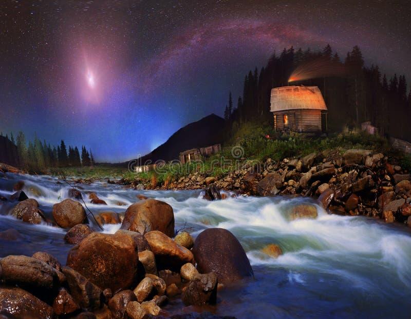 De melkweg en de maan over de bergen royalty-vrije stock foto