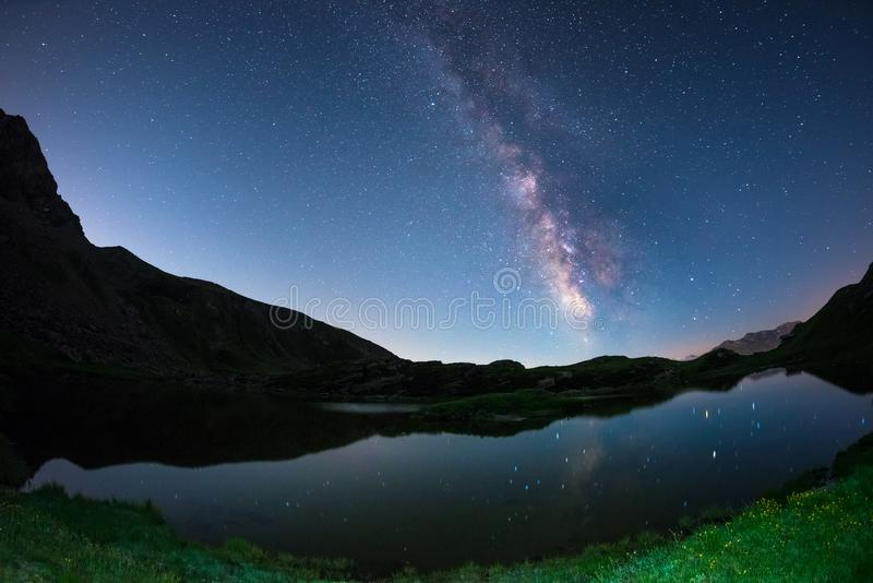 De melkwegboog en de sterrige hemel overdachten meer bij hoge hoogte op de Alpen Fisheye toneelvervorming en 180 graadmening royalty-vrije stock afbeeldingen