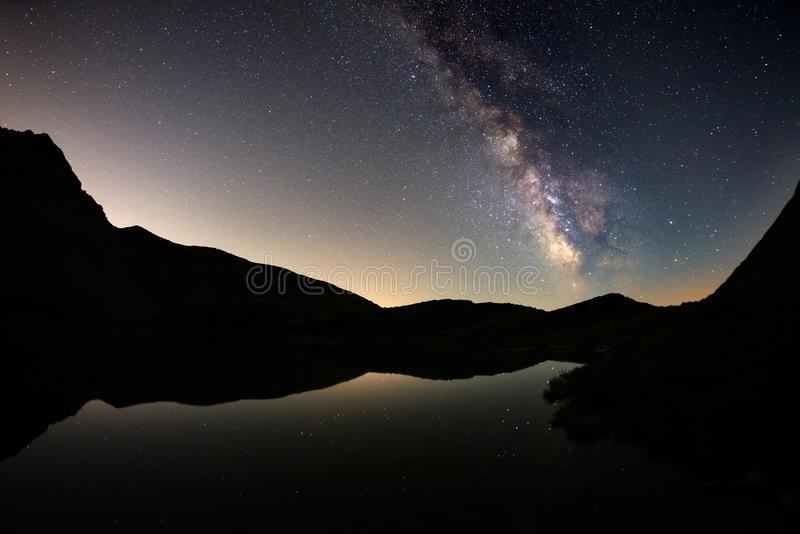 De melkwegboog en de sterrige hemel overdachten meer bij hoge hoogte op de Alpen Fisheye toneelvervorming en 180 graadmening royalty-vrije stock foto's