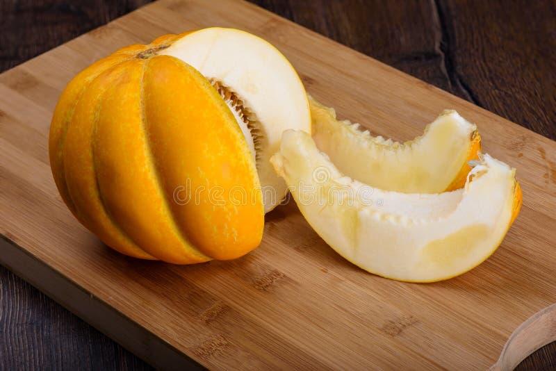 De meloen met twee sneed plakken op scherpe raad stock afbeeldingen