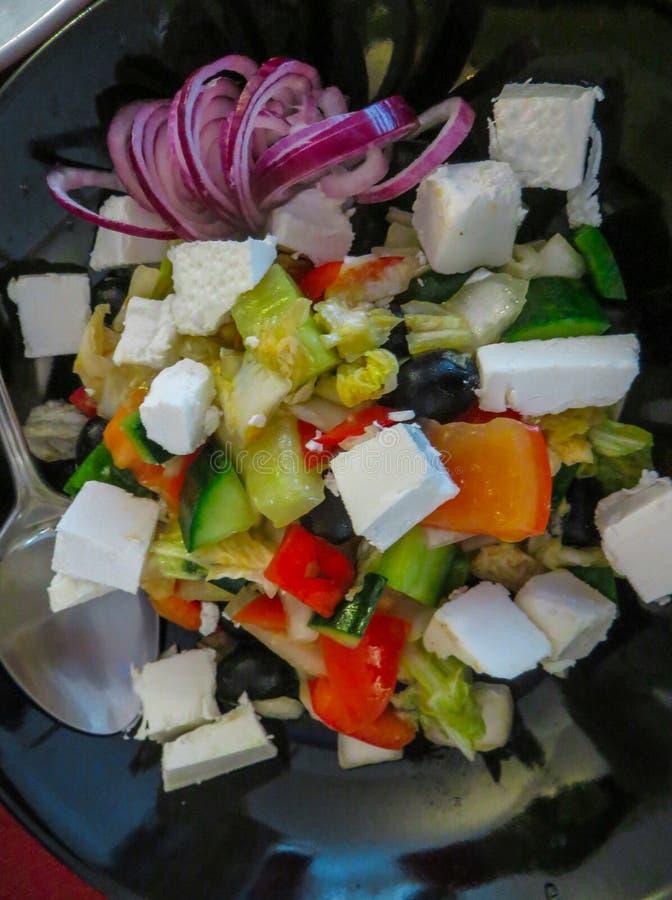 De mengeling doorbladert salade met tomaat, geroosterde en gepelde groene paprika, en feta-kaas gekleed met olijfolie, knoflook,  stock afbeeldingen