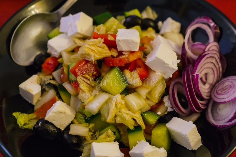 De mengeling doorbladert salade met tomaat, geroosterde en gepelde groene paprika, en feta-kaas gekleed met olijfolie, knoflook,  royalty-vrije stock fotografie