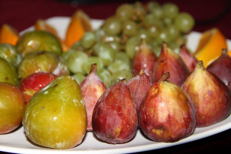 De mengeling van tropische organische vruchten diende op een plaat en kruiken verse sappen royalty-vrije stock afbeeldingen