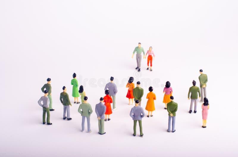 De menigte bekijkt de man en de vrouw die naar haar op een witte achtergrond komt Een man en een vrouw benaderen een groep peo stock afbeeldingen