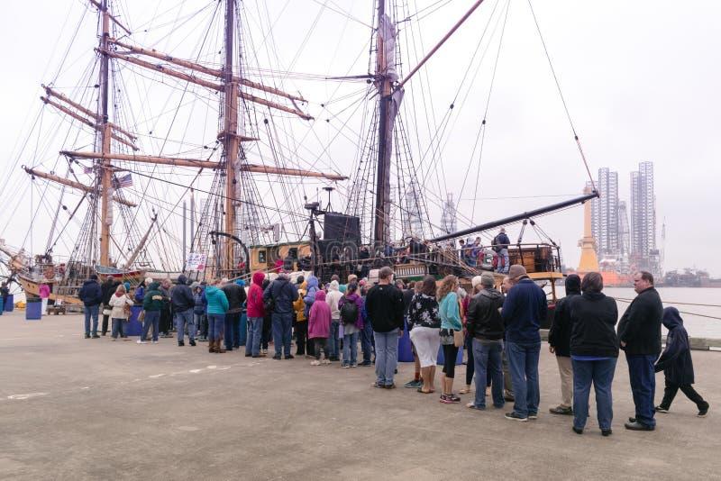 De menigte bevindt zich in lijn om een lang schip in te schepen royalty-vrije stock afbeelding