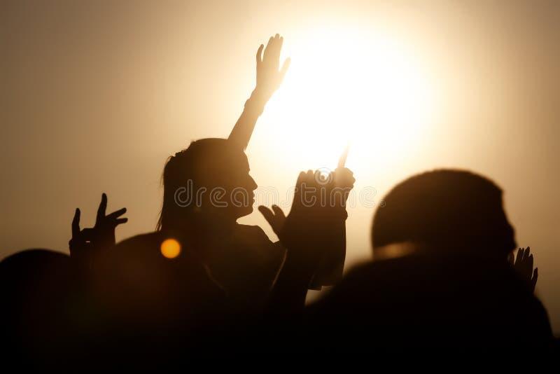 De menigte geniet omhoog van het festival van de de zomermuziek, zonsondergang, de silhouettenhanden royalty-vrije stock foto's
