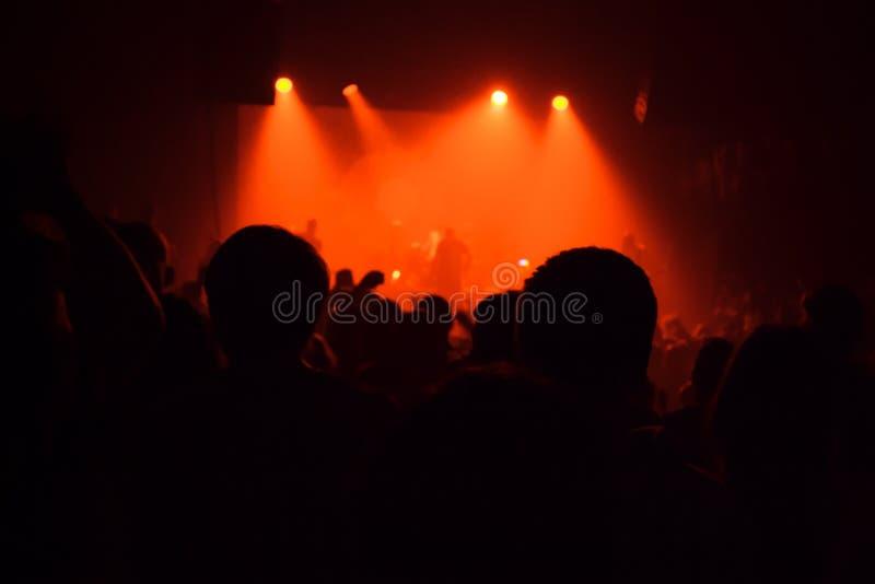 De menigte van publiekssilhouetten in grote concertzaal het letten op rots toont stock foto