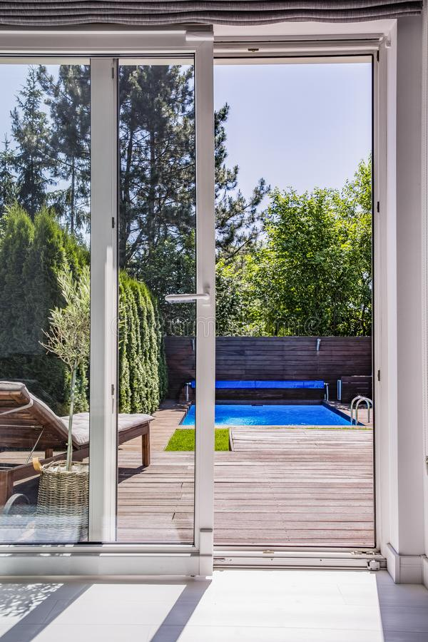 De mening door venster op terras met sunbed, zwembad en RT royalty-vrije stock afbeelding