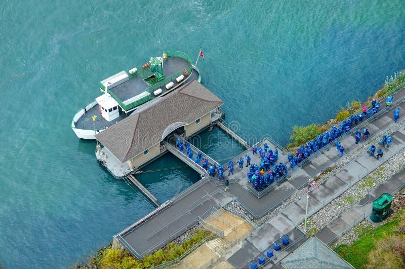 De mening over de Buffelsstad Niagara van de staat van New York valt de boot van sightseeingsreizen bij pijler en inschepende men royalty-vrije stock foto