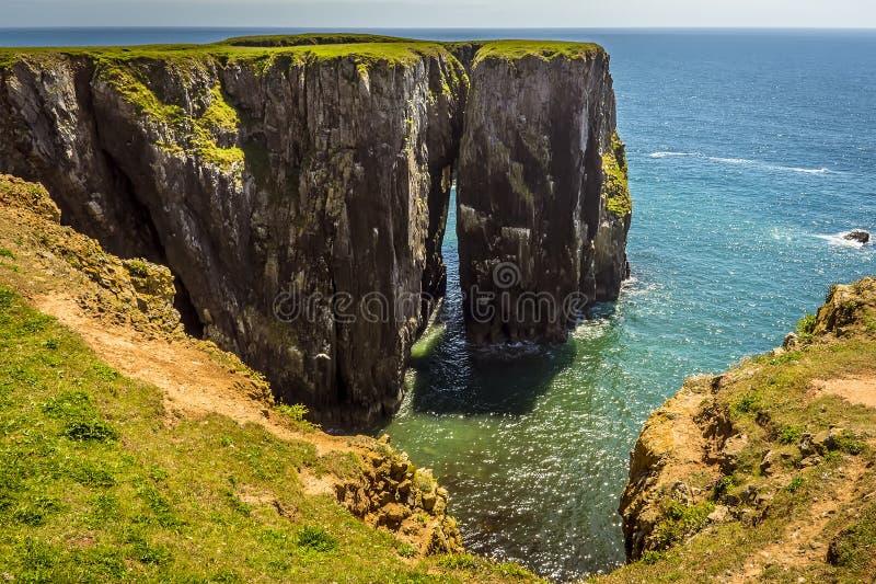 De mening tussen een rotsstapel en het vasteland op de Pembrokeshire-kust, Wales royalty-vrije stock foto's