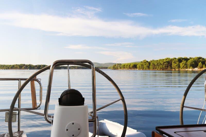 De mening van de achtersteven van een varend die jacht met twee handwielen wordt uitgerust op een mooie groene baai met een rotsa royalty-vrije stock foto