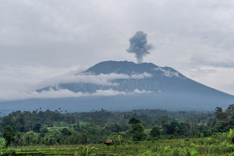 De mening van de Agungvulkaanuitbarsting dichtbij padievelden, Bali stock fotografie